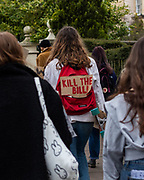 """A woman has the sign """"Kill the bill"""" attached to her backpack whilst marching against the newly introduced restrictions for the right to protest. Cheltenham 20/03/2021"""