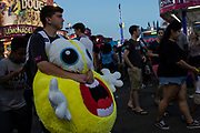 WASHINGTON, USA - August 19: A boy holds onto a giant stuffed toy won at one of the games at the Montgomery County Agricultural Fair in Gaithersburg, Md., USA on August 19, 2017.
