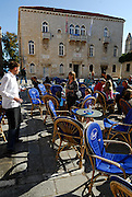 Tourist and waiter, outdoor cafe, Trogir old town, Croatia