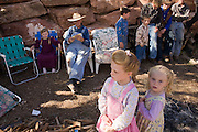 "Aug 9, 2008 -- COLORADO CITY, AZ: JOSEPH JESSOP, 86, patriarch of the Jessop family, polygamists and members of FLDS in Colorado City, AZ, surrounded by some of his great grandchildren during a picnic near their home in Colorado City, AZ. Colorado City and neighboring town of Hildale, UT, are home to the Fundamentalist Church of Jesus Christ of Latter Day Saints (FLDS) which split from the mainstream Church of Jesus Christ of Latter Day Saints (Mormons) after the Mormons banned plural marriage (polygamy) in 1890 so that Utah could gain statehood into the United States. The FLDS Prophet (leader), Warren Jeffs, has been convicted in Utah of ""rape as an accomplice"" for arranging the marriage of teenage girl to her cousin and is currently on trial for similar, those less serious, charges in Arizona. After Texas child protection authorities raided the Yearning for Zion Ranch, (the FLDS compound in Eldorado, TX) many members of the FLDS community in Colorado City/Hildale fear either Arizona or Utah authorities could raid their homes in the same way. Older members of the community still remember the Short Creek Raid of 1953 when Arizona authorities using National Guard troops, raided the community, arresting the men and placing women and children in ""protective"" custody. After two years in foster care, the women and children returned to their homes. After the raid, the FLDS Church eliminated any connection to the ""Short Creek raid"" by renaming their town Colorado City in Arizona and Hildale in Utah. A member of the Jessop family weeds the community corn plot in Colorado City, AZ. The Jessops are a polygamous family and members of the FLDS. Photo by Jack Kurtz / ZUMA Press"