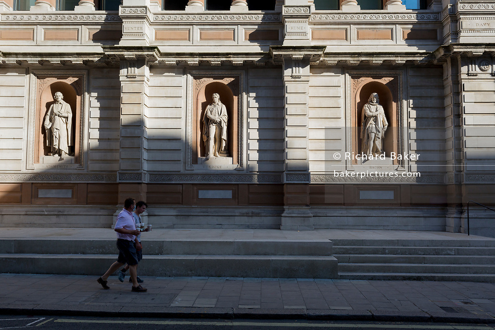 With a further 154 covid deaths reported in the last 24hrs, bringing the total to 43,081 in the UK during the Coronavirus pandemic, two men carry their takeaway coffees past the statues of Adam Smith, John Locke and Francis Bacon outside the rear entrance of the Royal Academy in Burlington Gardens, on 24th June 2020, in London, England.
