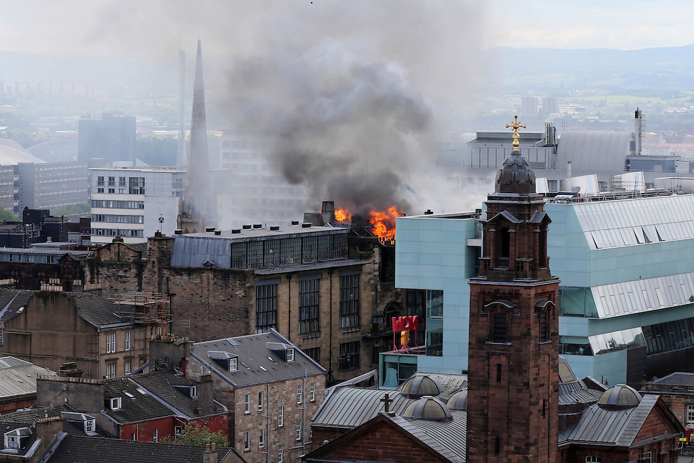 The Glasgow School of Art in flames. Firefighter try to control the blaze. Onlookers are in disbelieff and tears.  Picture Robert Perry 23rd May 2014<br /> <br /> Must credit photo to Robert Perry<br /> FEE PAYABLE FOR REPRO USE<br /> FEE PAYABLE FOR ALL INTERNET USE<br /> www.robertperry.co.uk<br /> NB -This image is not to be distributed without the prior consent of the copyright holder.<br /> in using this image you agree to abide by terms and conditions as stated in this caption.<br /> All monies payable to Robert Perry<br /> <br /> (PLEASE DO NOT REMOVE THIS CAPTION)<br /> This image is intended for Editorial use (e.g. news). Any commercial or promotional use requires additional clearance. <br /> Copyright 2014 All rights protected.<br /> first use only<br /> contact details<br /> Robert Perry     <br /> 07702 631 477<br /> robertperryphotos@gmail.com<br /> no internet usage without prior consent.         <br /> Robert Perry reserves the right to pursue unauthorised use of this image . If you violate my intellectual property you may be liable for  damages, loss of income, and profits you derive from the use of this image.