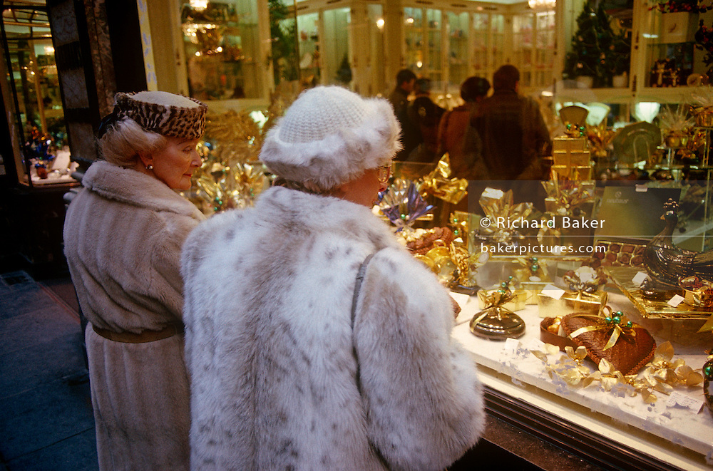 Two very posh Belgian ladies window shop in one of Belgium's smartest chocolatiers in the famous Galleries de la Reine in central Brussels. Wearing fur coats and warm hats, they epitomise wealth and prosperity in late 1980s Europe. Golden packaging is seen in this wonderful display where individual chocolates and shaped hearts and cakes show their exclusive values.