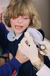 Doctor cutting off bandage on young girl's finger wound,