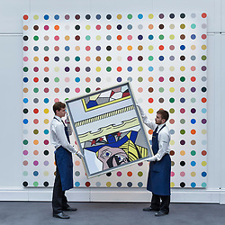 """© Licensed to London News Pictures. 23/06/2017. London, UK. Technicians show """"Two Paintings with Dado"""", 1983, by Roy Lichtenstein (estimate GBP2.4-3m) in front of """"1-Heptene"""", 2004-2011, by Damien Hirst (estimate GBP0.5-0.7m) at the preview of Sotheby's Contemporary Art Sale in New Bond Street.  The auction, which is dominated by Pop art, takes place on 28 June. Photo credit : Stephen Chung/LNP"""