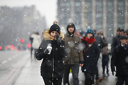 © Licensed to London News Pictures. 11/02/2017. London, UK. People walk across Westminster Bridge whilst snowing in London on Saturday, 11 February 2017. Photo credit: Tolga Akmen/LNP