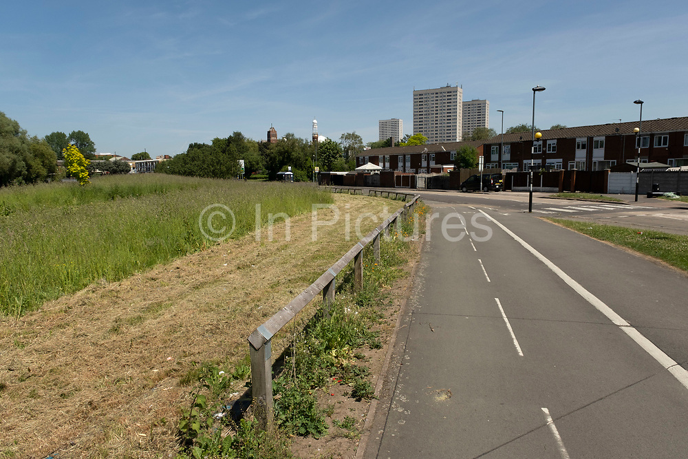 Cycle lane looking towards social housing estate high rise towers block in Highgate on 15th June 2021 in Birmingham, United Kingdom. Following the Big City Plan of February 2008, Highgate is now a district of Birmingham City Centre, yet is a very poor area of housing estates, lacking in investment.