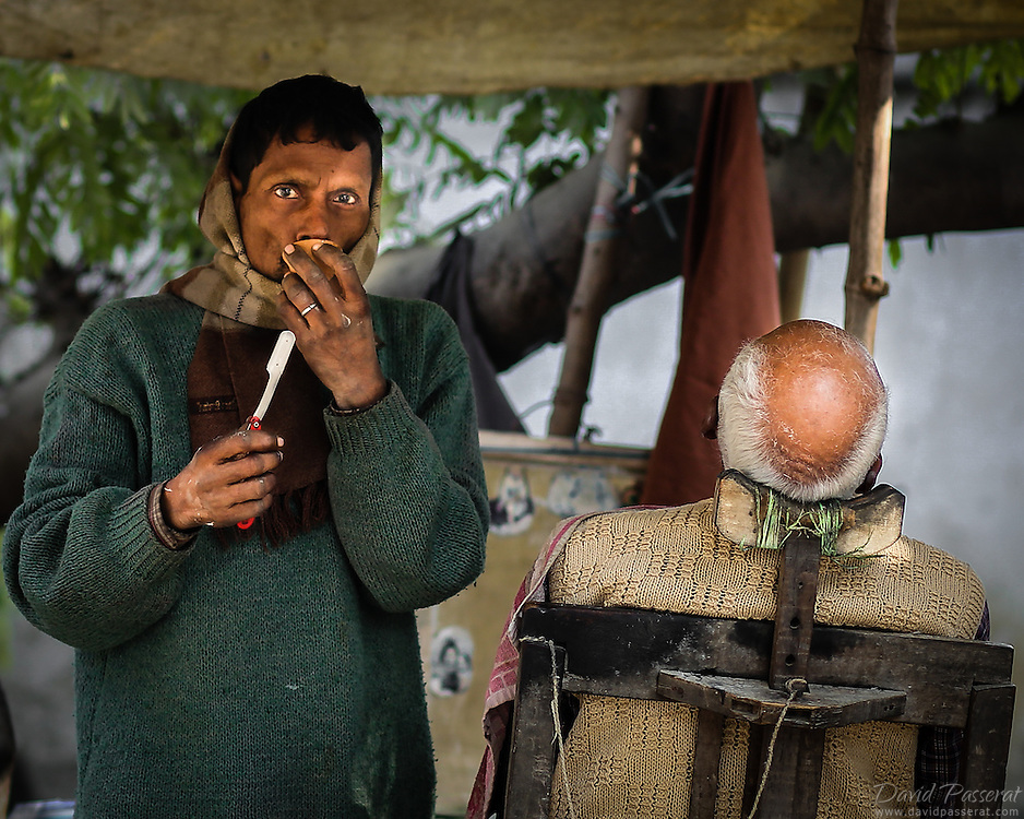 It is very commun in New Delhi to find barbers operating their work on the sidewalk.