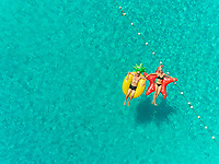 Aerial view of man and woman floating by string buoy on inflatable mattresses in transparent blue sea.