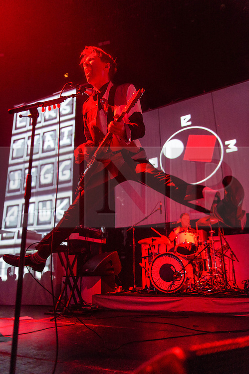 © Licensed to London News Pictures. 14/03/2014. London, UK.   Franz Ferdinand performing live at The Roundhouse. In this picture - Alex Kapranos.  Franz Ferdinand are a Scottish indie rock band composed of Alex Kapranos (lead vocals and guitar, keyboard), Bob Hardy (bass guitar), Nick McCarthy (rhythm guitar, keyboards and backing vocals), and Paul Thomson (drums, percussion and backing vocals). Photo credit : Richard Isaac/LNP