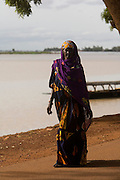 A woman strolling on the riverside on a sunday afternoon. At the confluence of the Niger and the Bani rivers, between Timbuktu and Segou, Mopti is the second largest city in Mali, and the hub for commerce and tourism in this west-african landlocked country.