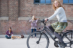 Woman riding bicycle on street with teenage girl playing violin in background, Munich, Bavaria, Germany