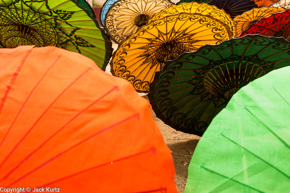 14 JUNE 2013 -  PATHEIN, AYEYARWADY, MYANMAR: Waterproof umbrellas  set out to dry at the Shwe Sar umbrella factory in Pathein. Pathein is a center of the Burmese umbrella and parasol industry. Most are actually parasols made in the traditional Burmese way using treated paper which is not water proof. Shwe Sar's umbrella's are made with treated cloth and are waterproof. Since US and European sanctions have been lifted businesses in Myanmar have seen an explosion in exports. Shwe Sar exports most of their umbrellas to Europe. Pathein, sometimes also called Bassein, is a port city and the capital of the Ayeyarwady Region, Burma. It lies on the Pathein River (Bassein), which is a western branch of the Irrawaddy River. It's the fourth largest city in Myanmar (Burma) about 190 km west of Yangon.   PHOTO BY JACK KURTZ
