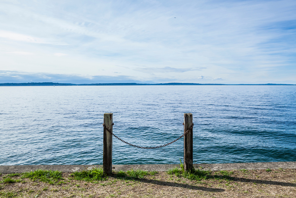 Looking out at the Puget Sound on the seawall in West Seattle where two posts with a chain between them stand.