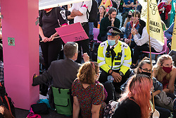 A Metropolitan Police officer asks environmental activists from Extinction Rebellion to move out from under a giant table used to block roads in the Covent Garden area during the first day of Impossible Rebellion protests on 23rd August 2021 in London, United Kingdom. Extinction Rebellion are calling on the UK government to cease all new fossil fuel investment with immediate effect. (photo by Mark Kerrison/In Pictures via Getty Images)