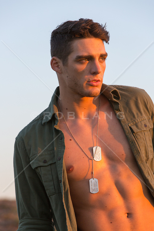 rugged man in an open army shirt and dog tags at sunset