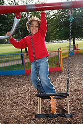 Boy standing on a swing