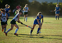 Newfound's Hannah Eastman and Gilford's Laurel Gingrich charge the ball during NHIAA Division III field hockey on Thursday afternoon.  (Karen Bobotas/for the Laconia Daily Sun)