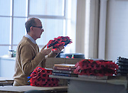 © Licensed to London News Pictures. 08/10/2014. Richmond, UK. A man prepares wreaths  made of poppies. The Mayor of London, Boris Johnson, and Zac Goldsmith MP tour 'The Poppy Factory' in Richmond, Surrey, today 9th October 2014.  Melanie Waters, the Chief Executive, briefed the Mayor and Zac Goldsmith on The Poppy Factory's 'Getting You Back to Work' initiative. To date, The Poppy Factory has supported nearly 500 wounded, injured or sick ex-service men and women back into the workplace through this new, nationwide initiative, through connections with commercial organisations like Transport for London. The goal is to help over 1,000 veterans by 2018. Employees at The Poppy Factory have made some 13 million poppies, 950,000 thousand remembrance crosses and 96,000 wreaths for The Royal British Legion Remembrance events in November. The Annual Field of Remembrance at Westminster Abbey is also planned and delivered by The Poppy Factory. Photo credit : Stephen Simpson/LNP