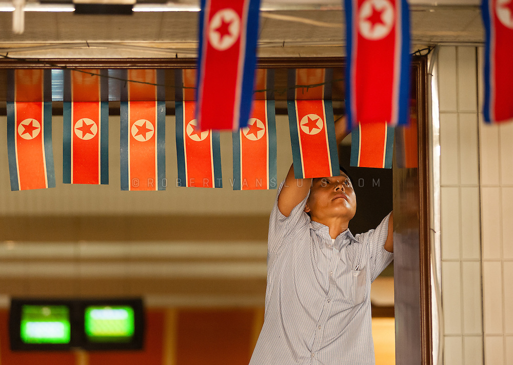 Putting up flags in honor of Liberation Day at the Golden Lane bowling alley, Pyongyang, DPRK (North Korea)