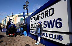 A general view of a young Chelsea fan in front of a Stamford Bridge sign prior to the Premier League match at Stamford Bridge, London.