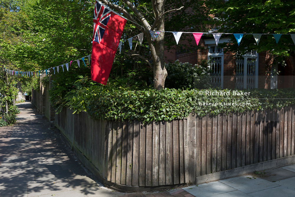 As the Coronavirus lockdown continues over the May Bank Holiday, the nation commemorates the 75th anniversary of VE Day (Victory in Europe Day, the day that Germany officially surrendered in 1945) and neighbours and residents emerge from their homes to party while still observing social distancing rules. A naval Union Jack Ensign flag hangs from a corner property in Camberwell, on 8th May 2020, in London, England.