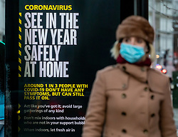 © Licensed to London News Pictures. 31/12/2020. London, UK. Members of the public walk past a Covid-19 information display in Fulham, South West London, warning the public to 'Stay Home' over the New Year as Covid-19 infection rates surge in the capital and the rest of the UK. Health Secretary Matt Hancock has ordered 20 million people into tier 4 Covid lockdowns which came into effect today, (New Years Eve) as the virus continues to spread through the country. Yesterday, the Oxford vaccine was approved for use, with the government securing over 100 million doses with an expected full rollout of vaccinations from January 4th 2021. UK. Photo credit: Alex Lentati/LNP