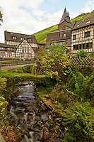 View of half-timbered homes, a brook, and private gardens, sitting below the vineyards and hills of Bacharach, Germany.