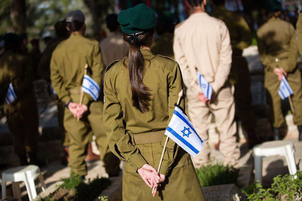 Israeli soldiers stand with Israeli national flags before placing them on graves of fallen soldiers, during a memorial ceremony at the Mount Herzl military cemetery in Jerusalem, Israel, on April 19, 2015, ahead of the annual Memorial Day honoring fallen soldiers and Victims of Terrorism, which begins Tuesday night.