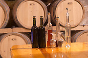 Oak barrels stacked in the wine cellar. Bottles on a table and glasses. Matusko Winery. Potmje village, Dingac wine region, Peljesac peninsula. Matusko Winery. Dingac village and region. Peljesac peninsula. Dalmatian Coast, Croatia, Europe.