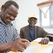 CAPTION: Guided by Mr Bonomar, Calisto Tocatia learns the Braille alphabet. He uses a sharp tool to mark a card by spiking through the tiny holes of a Braille stencil, thereby forming letters. Along with such education activities, training in other areas like small business management is also on offer for members. With specialised trainings and follow-up from CU, the lives of ACAMO's members have changed considerably. CU believes in strong community-led development, and creating unity among the organisation's members through workshops and mobilisation was the first step in reaching even more PWDs. ACAMO calculates that its work has now touched 448 of Niassa's 485 visually impaired people. LOCATION: Lulimile Village, Lichinga, Niassa Province, Mozambique. INDIVIDUAL(S) PHOTOGRAPHED: Calisto Tocatia (left) and Fernando Joaninha (right).