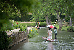 © Licensed to London News Pictures. 04/06/2021. Oxford, UK. A member of the public is seen sheltering underneath an umbrella while punting on the River Cherwell in central Oxford, England, on a wet and overcast day. The UK is experiencing damp and overcast conditions following a week of annual high temperatures. Photo credit: Ben Cawthra/LNP