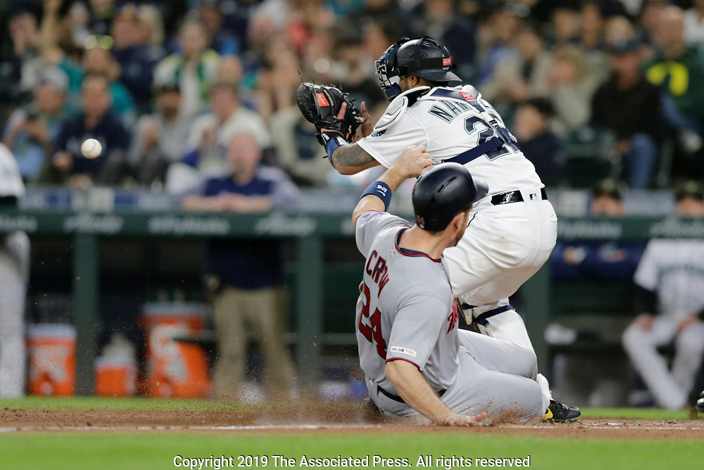 Minnesota Twins' C.J. Cron scores on a sacrifice fly while Seattle Mariners catcher Omar Narvaez waits for the throw during a baseball game, Saturday, May 18, 2019, in Seattle. (AP Photo/John Froschauer)