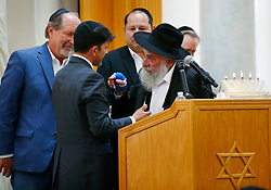 April 29, 2019 - Poway, California, U.S. - OSCAR STEWART, left, who was called a hero in the Poway shooting, is hugged by RABBI YISROEL GOLDSTEIN as Poway Mayor STEVE VAUS, left, looks on during a service for Lori Gilbert-Kaye, 60, at the Chabad of Poway. Gilbert-Kaye was killed by a gunman at the synagogue. (Credit Image: © K.C. Alfred/San Diego Union-Tribune via ZUMA Wire)