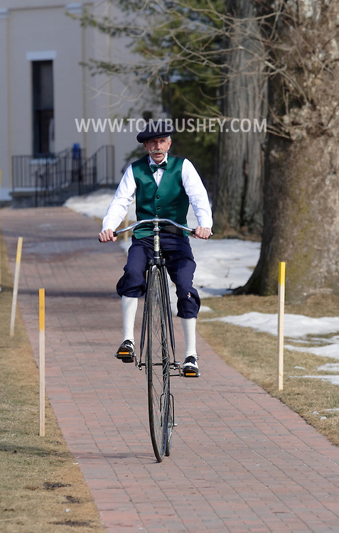 Goshen, New York - A man wearing period costume rides an antique high wheel bicycle on the sidewalk after taking part in the Mid-Hudson St. Patrick's Day parade on March 11, 2007.