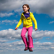 Molly levitates in bright colors on top of Eagle Rock in Breakheart Reservation, Wakefield, MA