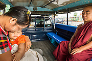 """24 MAY 2013 - MAE SOT, THAILAND:    A Burmese woman and her child with a Burmese Buddhist monk in the back of a """"songthaew"""" going to Mae Sot, Thailand. A """"songthaew"""" is a pickup truck converted to use as a bus. They're common in Southeast Asia.  PHOTO BY JACK KURTZ"""