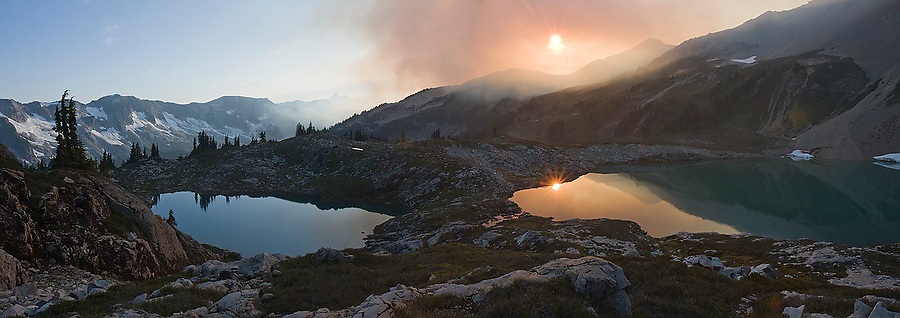 Sunlight is turned orange by smoke from a nearby forest fire rising over the beautiful alpine basin at Tapto Lakes, North Cascades National Park, Washington.