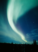 Beautiful display of northern lights arcing over the Alaska Range including the Tokosha Mountains, Denali State Park, Alaska.