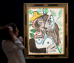 """© licensed to London News Pictures. London, UK  17/06/2011. A Sotheby's worker admires """"Couple Le Baiser' by Pablo Picasso, which is estimated to fetch up to £8 million at auction as part of Sotheby's upcoming auction of  Impressionist and Modern art. Please see special instructions for usage rates. Photo credit should read Ben Cawthra/LNP"""