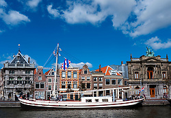 Boat moored on River Spaarne and historic houses in Harlem Netherlands