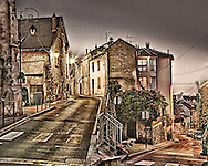 The street corner in Carrieres-sur-Seine, France made famous in the painting done by Maurice de Vlaminck.  The glow of different colored street lights causes the rouge and yellow in the scene.  Aspect Ratio 1w x 0.8h.