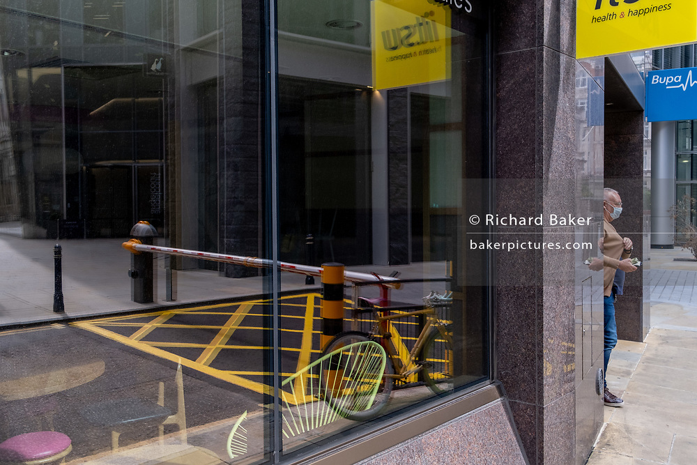 As workers in London largely remain working from home during the Coronavirus pandemic, a City worker emerges from a doorway next to a reflection of a locked bike, a traffic grid and street barrier in the City of London, on 4th September 2020, in London, England.