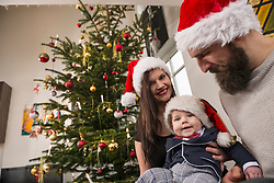 Parents with baby boy wearing Santa hat