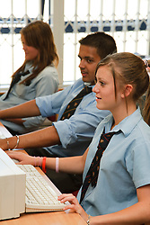 Pupils in school library looking at computers.