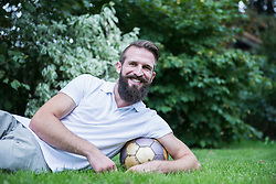 Young man with football under his arm lying in garden, Bavaria, Germany