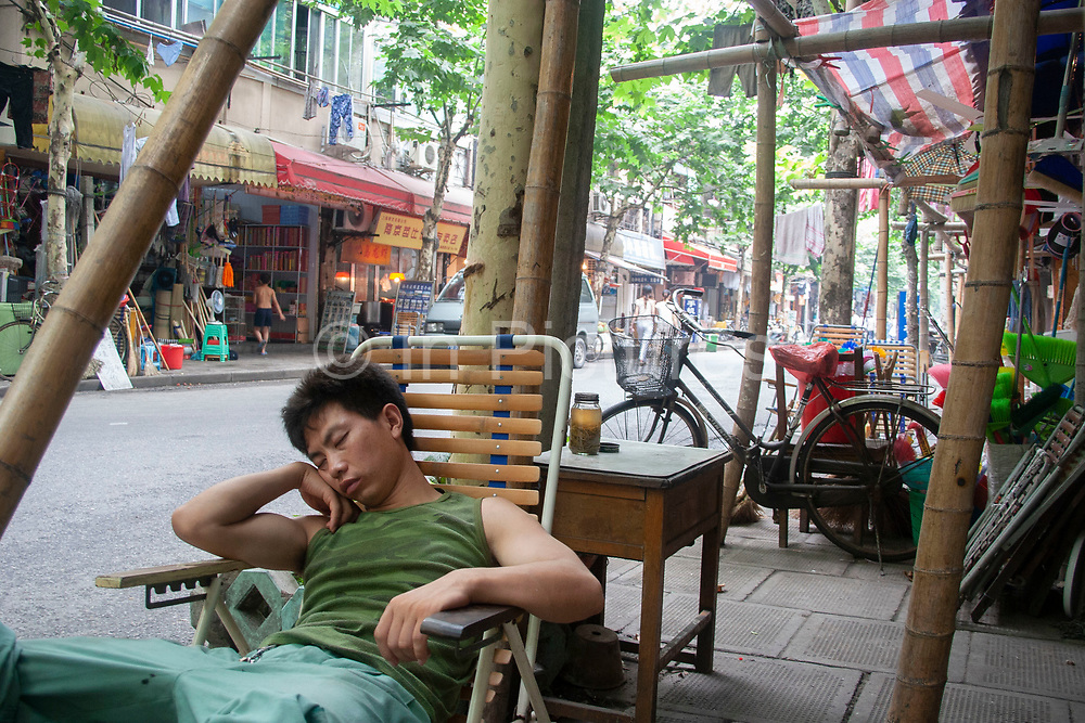 A Shanghainese man sleeps in the afternoon heat on Xiangshan Road (Xiangshan Lu) am area of Shanghai where artists studios and galleries have sprung up in the last years. Sleeping during the day is a common part of life on the city streets. The heat can be draining especially to those doing physical work. Bamboo scaffolding is still a common sight in China and provides incredibly strong structures.