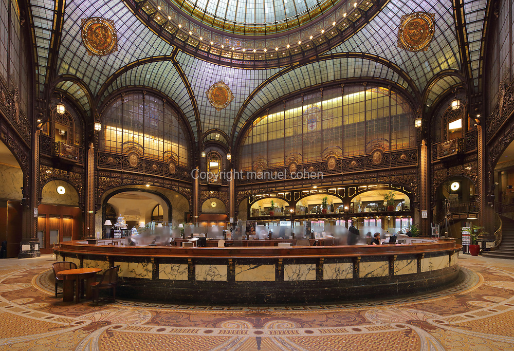 Hall, 4 storeys high and topped with a pinnacled dome made from glass and a self-supporting steel structure, in the registered head office of Societe Generale, at 29 Boulevard Haussmann in the 9th arrondissement of Paris, France. Below is 'the cheese', a large circular counter, and behind, the mezzanine office level created in 1919. The steel structure was made by Moysant-Laurent and Savey at the Imphy steelworks. The glazed 18m wide dome was made by Jacques Galand. The bank was founded in 1864 and these buildings were transformed 1906-12 by Jacques Hermant, and in use from 1915. Societe Generale remains one of the largest banks in the world, although its headquarters are now at La Defense. The Haussmann building is listed as a historic monument. Picture by Manuel Cohen
