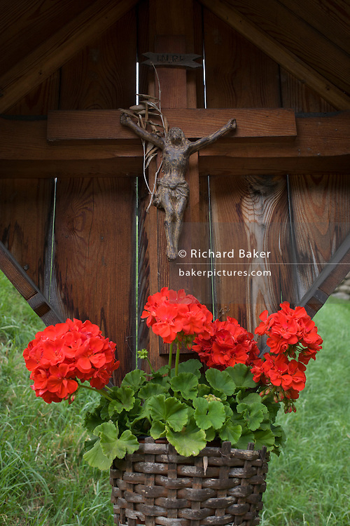 Rural crucifix and red flowers on a roadside shrine on the Jaufenpass in South Tyrol, northern Italy.