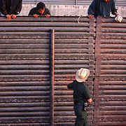 Migrants climb the US Mexico border fence to view life on the US side of the border.
